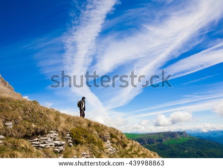 Beautiful amazing day summer mountains. A man goes a sport hike in holidays. Nature background. Northern country Russia Caucasus wilderness. Rocky route. Blue sky. Inspiring leisure. - stock photo