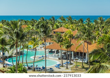 beautiful, amazing gorgeous view of tropical garden with people in background against tranquil azure ocean and blue sky - stock photo
