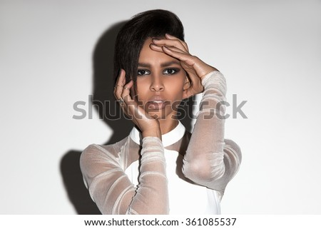 Beautiful american african girl posing. Woman with brown hair, in white dress, beauty, dark skin. Attractive, sexy fashion model. Shot in studio, on white background.  Hands posing, make up, shadow. - stock photo