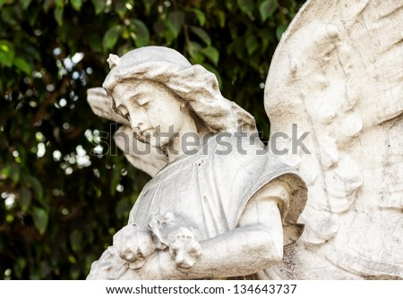 Beautiful ancient female angel  sculpture with a diffused green vegetation background - stock photo