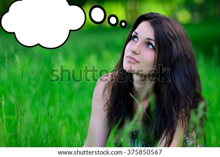 Beautiful and attractive girl thinks about something and looks up.Thoughts in the form of clouds.Nice,love girl dreams about something. - stock photo