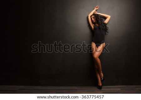 Beautiful and attractive girl with thick wavy hair, sexy figure and long legs posing in the black body  - stock photo