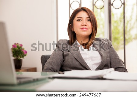 Beautiful and confident business woman looking serious and making eye contact - stock photo