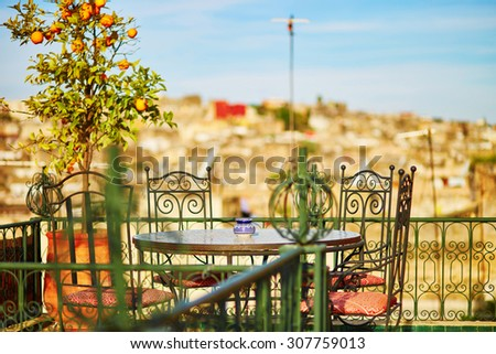 Beautiful and cozy Moroccan restaurant with orange tree in Fes, Morocco - stock photo