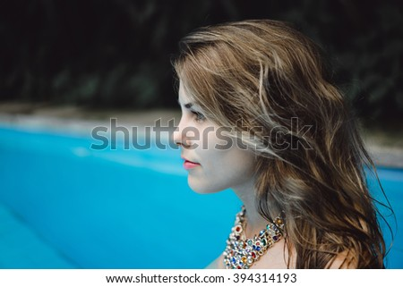 Beautiful and cute girl posing in a blue swimming pool in an elegant necklace. A girl with long blond hair , with an incredibly beautiful and piercing eyes and stare. fashion. - stock photo