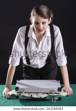 Beautiful and dangerous. Young female gangster. On the green table a bag of cash. - stock photo