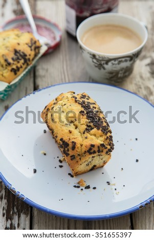Beautiful and delicious homemade bread with chocolate chips, your perfect breakfast or afternoon tea. With fresh brewed espresso and jam. On wooden table.  - stock photo