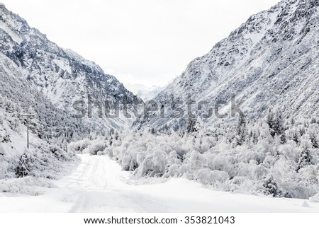 Beautiful and dramatic winter scene in the snowy mountain region of Ala Archa National Park, Kyrgyzstan. An icy road leads into a steep snow covered mountain valley. - stock photo