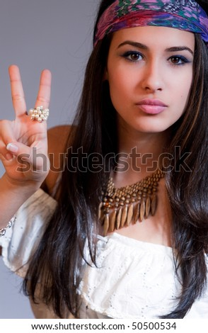 Beautiful and exotic young woman of multiple ethnicity waiving peace sign with 1960s wardrobe similar to a hippie. - stock photo