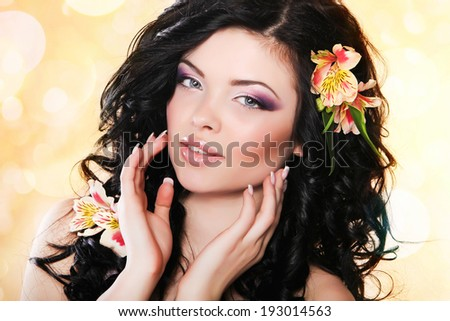 Beautiful and Fashion Sexy young woman with  flowers on her long hair. Vogue style model girl face with flowers. Manicure and Makeup  - stock photo