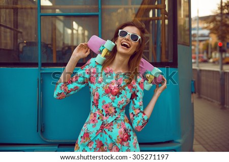 Beautiful and fashion young woman model posing with a skateboard on city street - stock photo