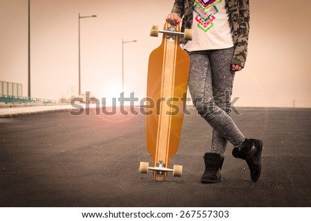 Beautiful and fashion young woman posing with a skateboard .Lens flare - stock photo