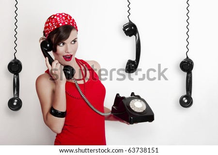 Beautiful and fashion young woman with a pin-up look. posing with a vintage phone - stock photo