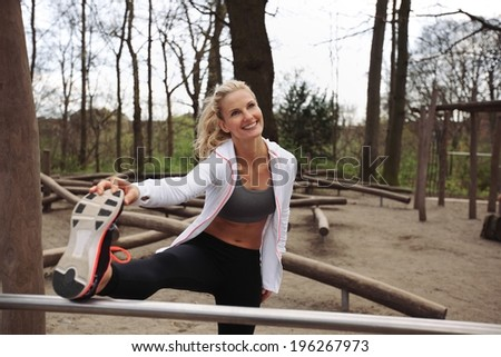 Beautiful and fit young woman stretching before a run. Young female runner stretching her muscles before a training session. - stock photo