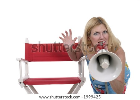 Beautiful and glamorous woman standing beside a red director's chair and holding a megaphone. - stock photo