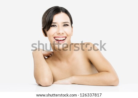 Beautiful and happy asian woman with arms over a white table - stock photo