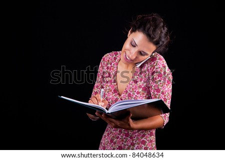 beautiful and happy businesswoman taking notes on the phone, isolated on black, studio shot - stock photo
