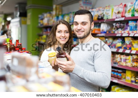 Beautiful and happy lovers buying convenience food in a local shop - stock photo