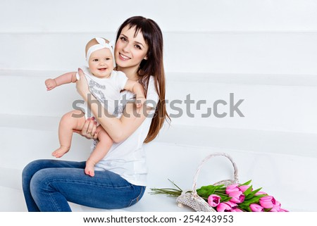Beautiful and happy mom brunette in white t-shirt and jeans holding a little smiling baby daughter on a white background in the Studio, next to the tulips - stock photo