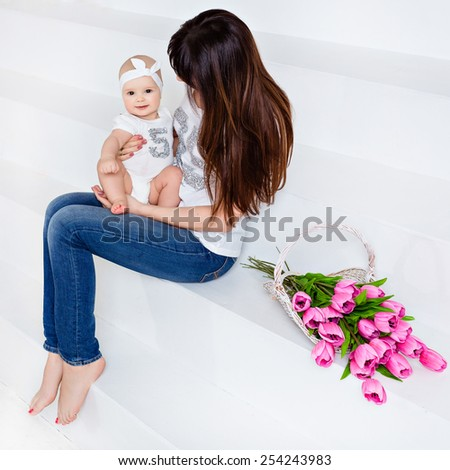 Beautiful and happy mom brunette in white t-shirt and jeans holding on her knees a little smiling baby daughter on a white background with tulips - stock photo