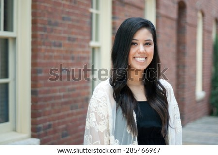 Beautiful and happy senior graduate standing in front of building wearing a dress. - stock photo