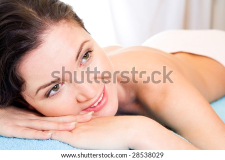 Beautiful and happy woman waiting for massage in spa salon - stock photo