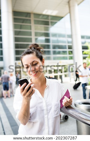 Beautiful and happy young businesswoman looking on cell phone in front of the airport - stock photo