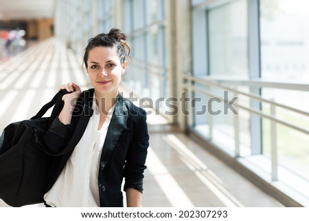 Beautiful and happy young businesswoman walking in the hall of  airport with her luggage. - stock photo