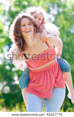 Beautiful and happy young mother giving piggyback ride to her daughter. Both smiling. Summer park in background. - stock photo
