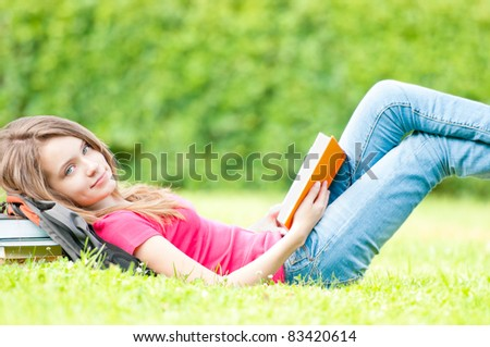 beautiful and happy young student girl lying on grass with opened book, smiling and looking into the camera. Pile of books under her head. Summer or spring green park in background - stock photo