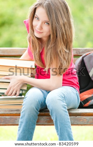 beautiful and happy young student girl sitting on bench and lifting heavy pile of books with her hands, smiling and looking into the camera. Summer or spring green park in background - stock photo