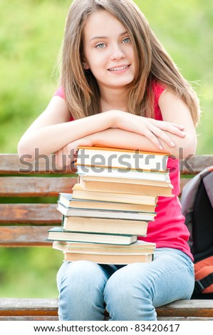 beautiful and happy young student girl sitting on bench, her hands on pile of books, looking into the camera and smiling. Summer or spring green park in background - stock photo