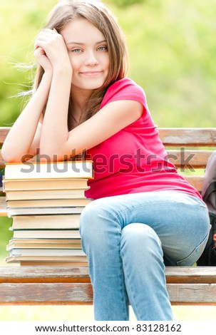 beautiful and happy young student girl sitting on bench, her hands on pile of books, smiling and looking into the camera. Summer or spring green park in background - stock photo