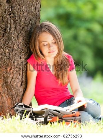 beautiful and happy young student girl sitting on green grass under the tree, smiling and reading book. Summer or spring green park in background - stock photo