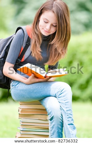 beautiful and happy young student girl sitting on pile of books, holding book in her hands and reading. Backpack on her shoulder. Summer or spring green park in background - stock photo
