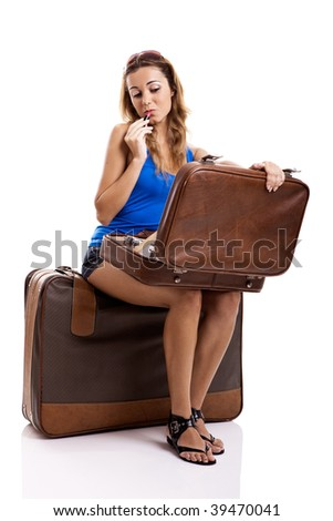 Beautiful and happy young woman applying makeup, with a opened old leather suitcase - stock photo