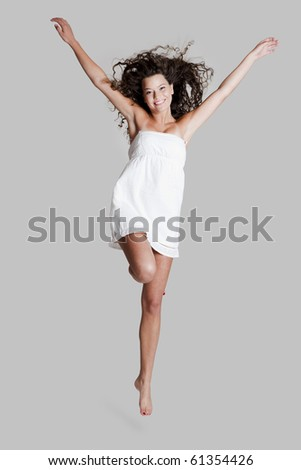 Beautiful and happy young woman jumping over a grey background - stock photo