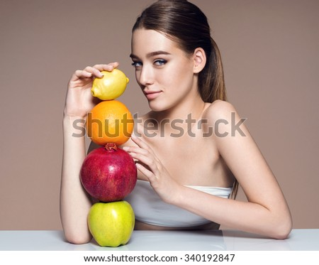 Beautiful and Healthy skin, natural organic raw fresh food concept / portrait of girl with fruits mix on the table over beige backdrop. High resolution product. - stock photo