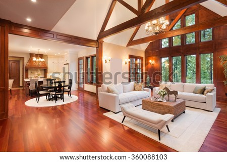 Beautiful and  huge living room with hardwood floors, tall vaulted ceiling, fireplace and couch in new luxury home. Has view of kitchen - stock photo