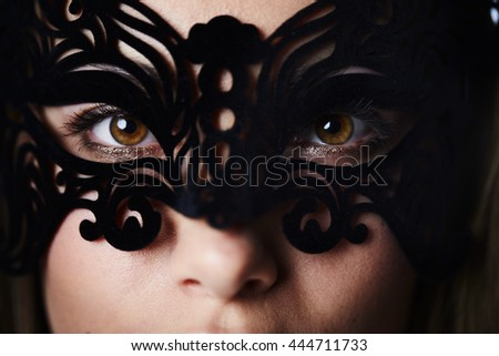 Beautiful and masked woman with brown eyes, close up - stock photo