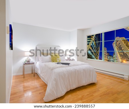 Beautiful and modern home and hotel bedroom interior design with fantastic window view at night city. - stock photo