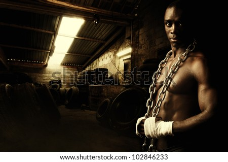 Beautiful and muscular black man with chains in dark background - stock photo