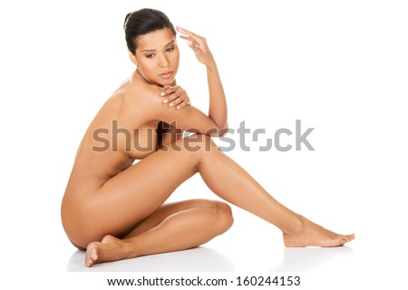 Beautiful and naked woman sitting. Side view. Legs half-straight. Isolated on white.  - stock photo