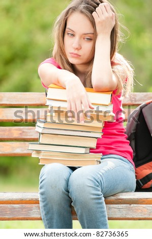 beautiful and sad young student girl sitting on bench with pile of books under her hands. She is depressed and looking away from the camera. Summer or spring green park in background - stock photo