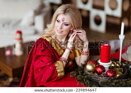 Beautiful and sensual blonde girl in Indian red saree sitting at the holiday table and looking away - stock photo