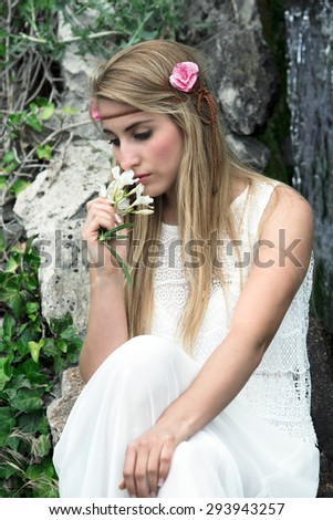 beautiful and sensual woman with long blond hair smelling some flowers from the garden / melancholic portrait of cute blonde woman smelling flowers - stock photo