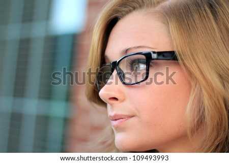 Beautiful and Serious Business Woman Wearing Eye Glasses Looking Straight Ahead - stock photo
