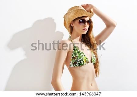 Beautiful and sexy blond girl in bikini and sun glasses with hair style posing on white - stock photo