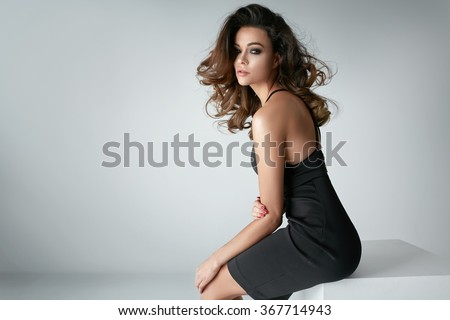Beautiful and sexy brunette in a black dress - stock photo