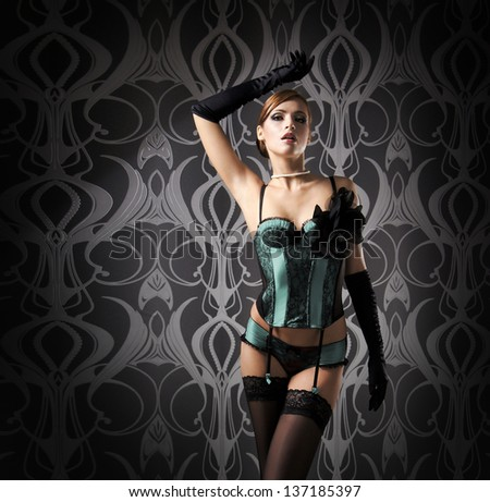 Beautiful and sexy cabaret artist in lingerie over vintage background - stock photo